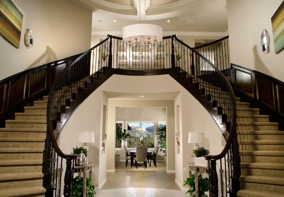 An Impressive Two Story Foyer Showcases A Beautiful Dual Staircase