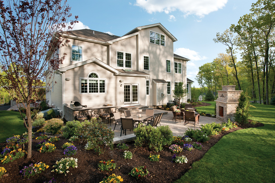 The Duke Home Design With Outdoor Stone Fireplace On Patio