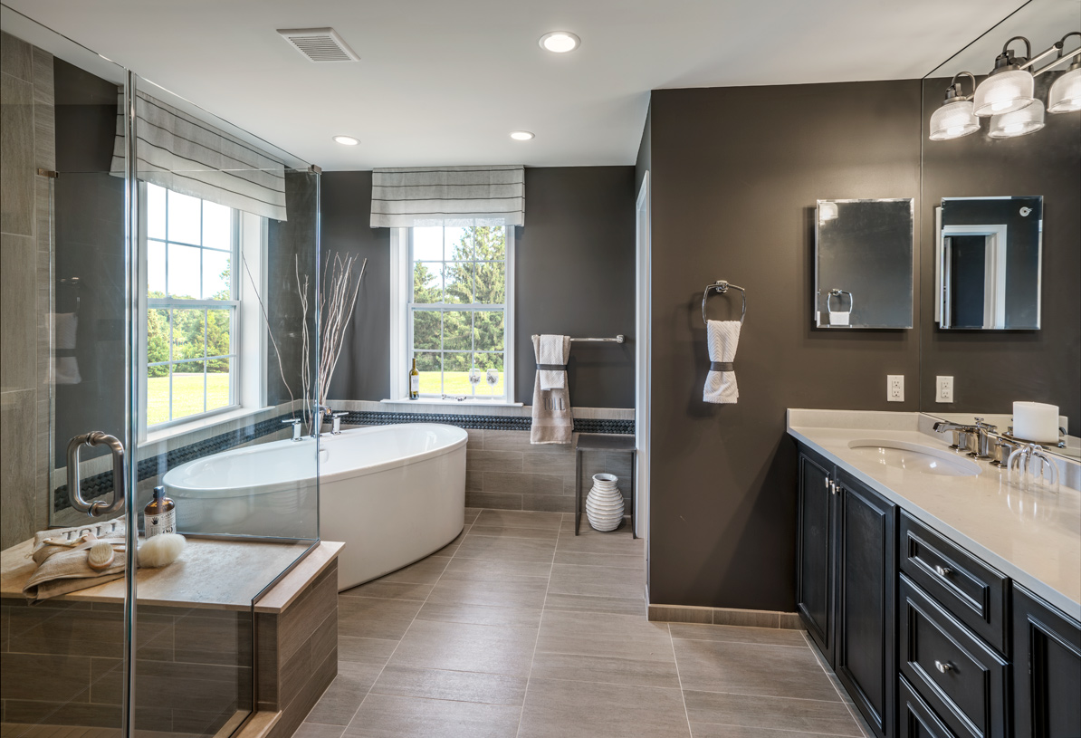 Primary bedroom suite with luxury bath, shower with seat, and dual-sink vanity