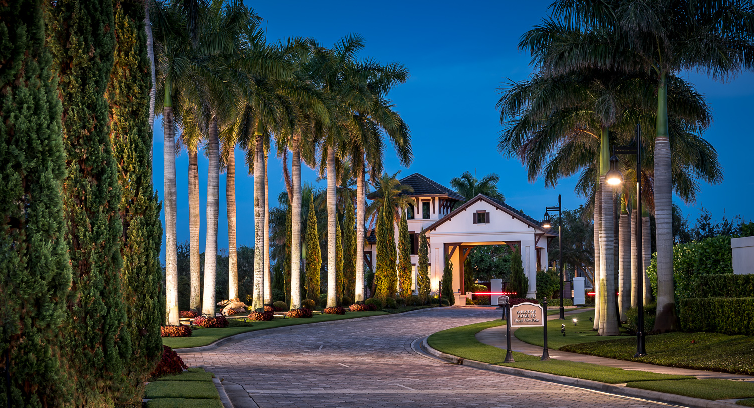 The elegant entry is lined with royal palms