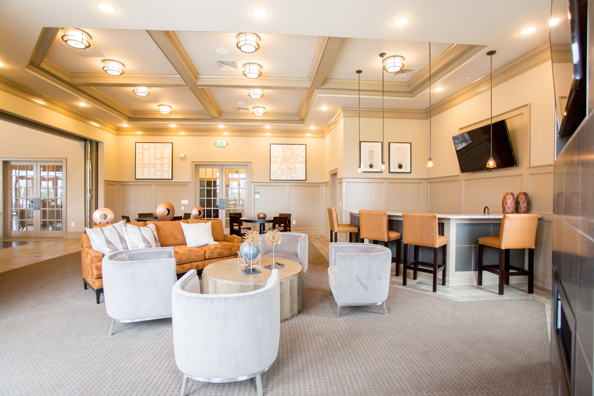 The lounge at the clubhouse features a bar, comfortable seating, and multiple tvs