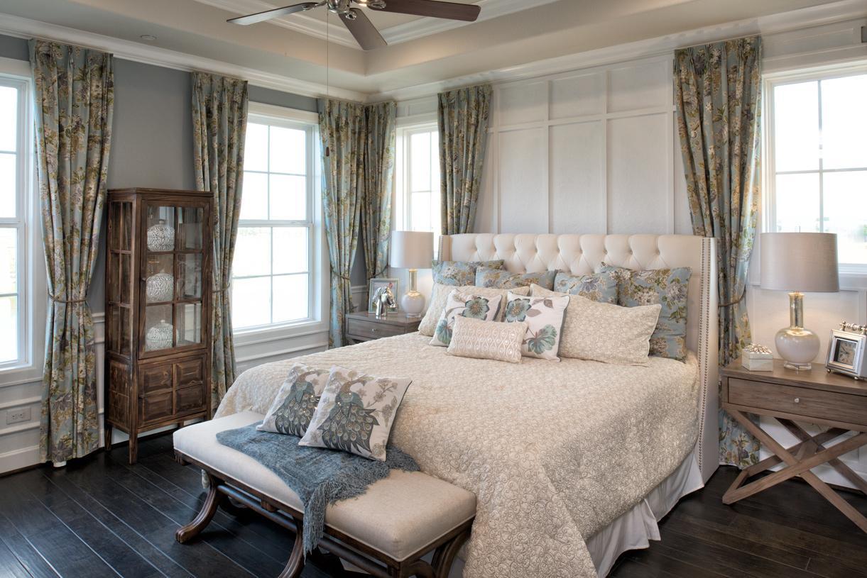 Luxurious primary bedroom with wood flooring