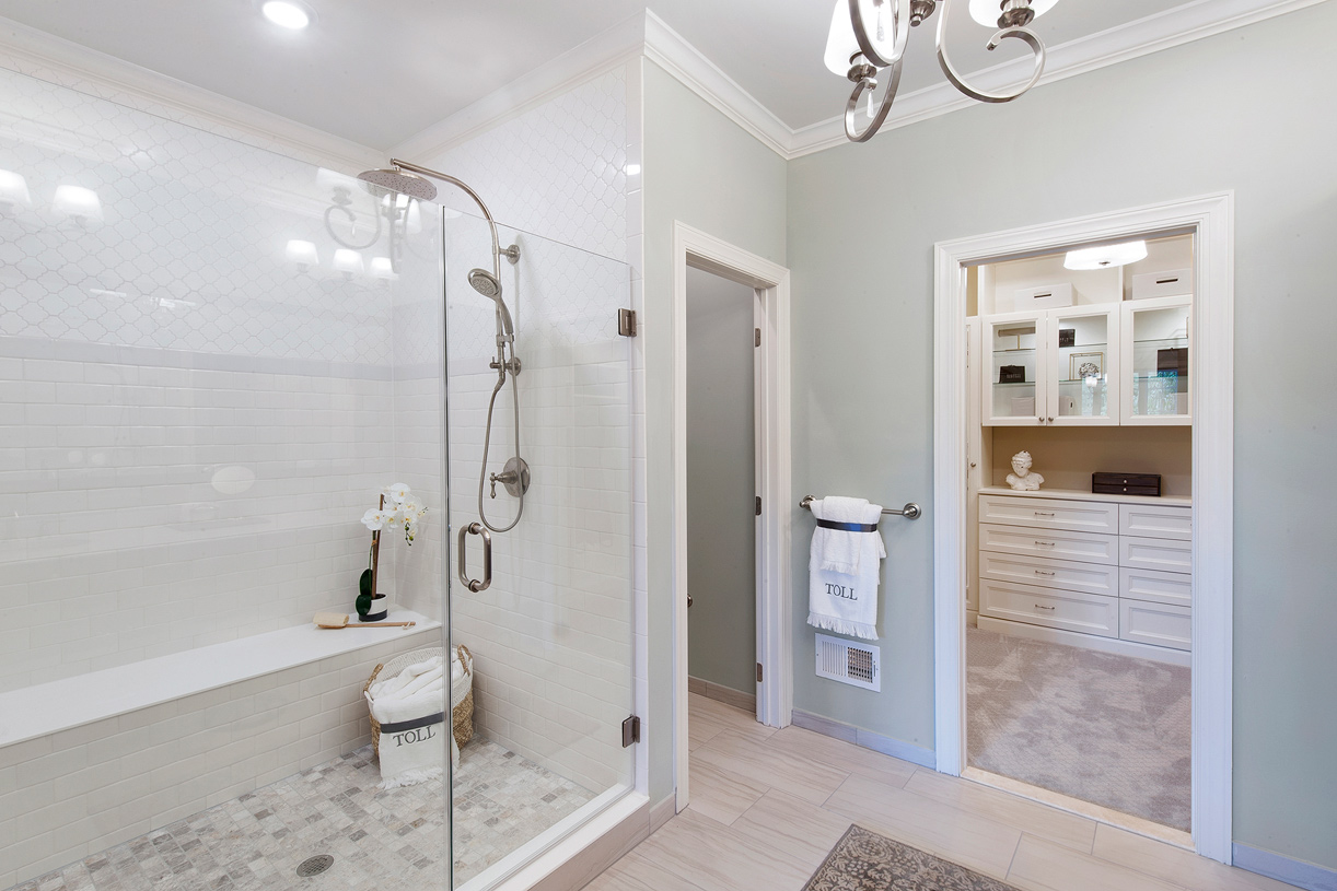 The luxury primary bathroom includes frameless glass shower