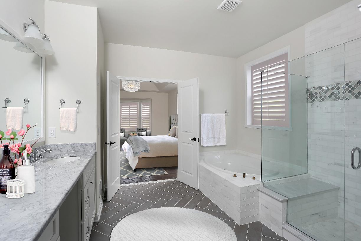 Luxurious primary bath features soaking tub, shower, dual vanity sinks, and private toilet area