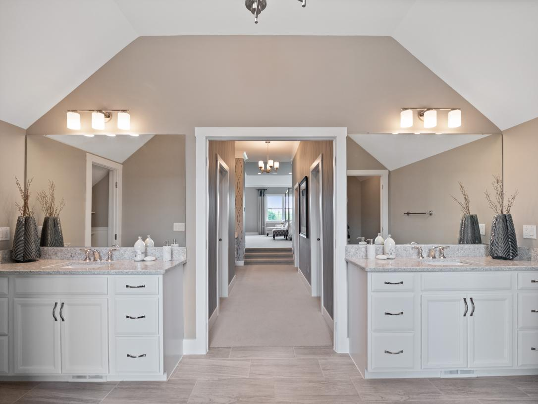 Primary bath dual vanity sinks and walk-in closet hallway