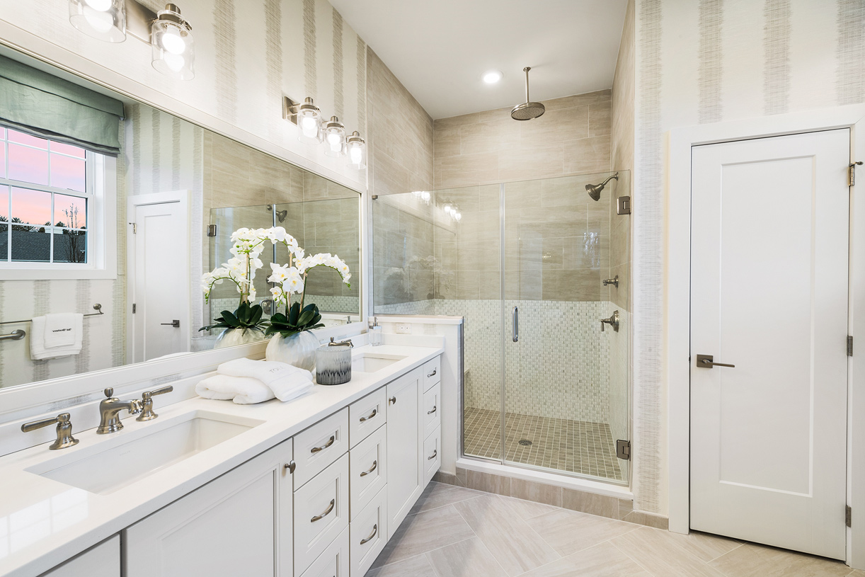 A relaxing and spacious primary bath has a dual sink vanity and oversized shower