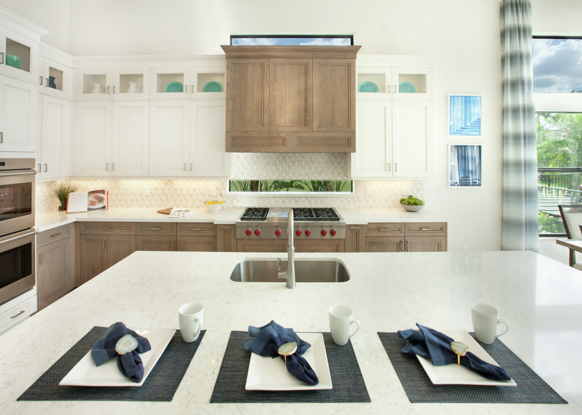 Kitchen includes designer upper cabinets plus windows above and below the cooktop