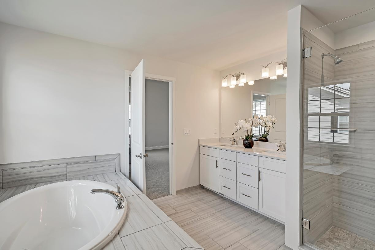 Standard primary bath complete with dual vanity sinks, soaking tub, and shower
