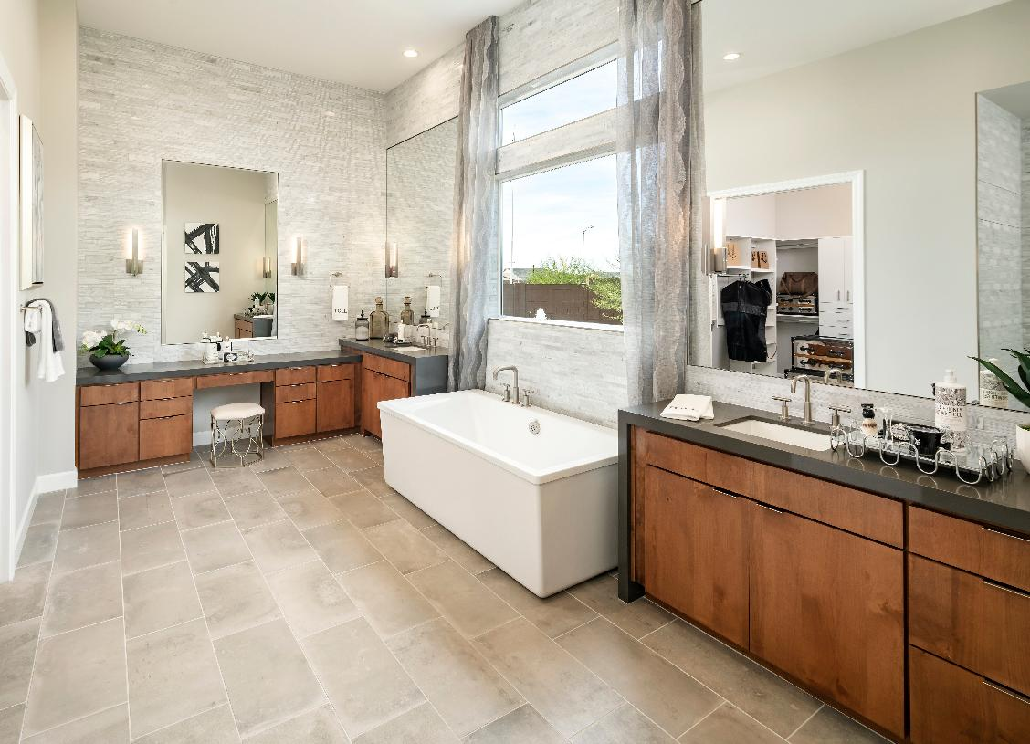Luxe primary bath with separate vanities, soaking tub, and walk-in shower