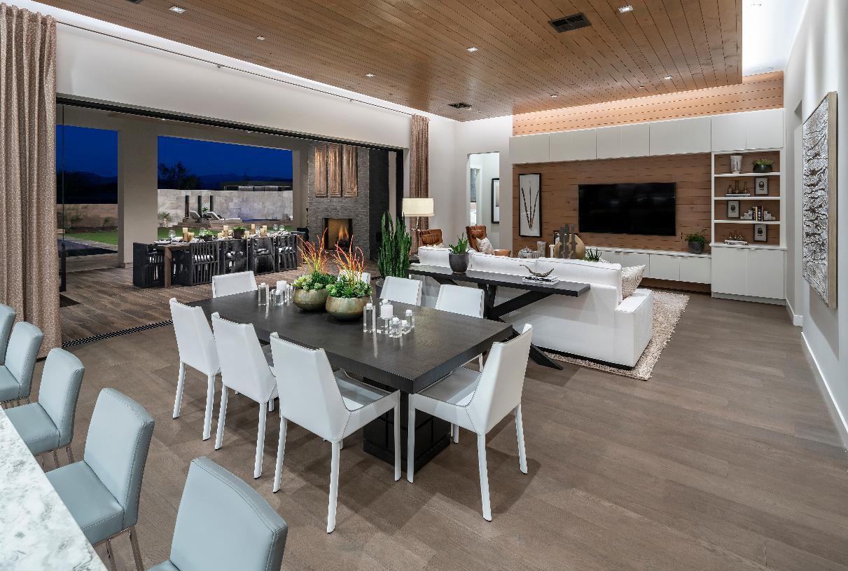 Soaring great room and dining room, with a view of the expansive covered patio beyond