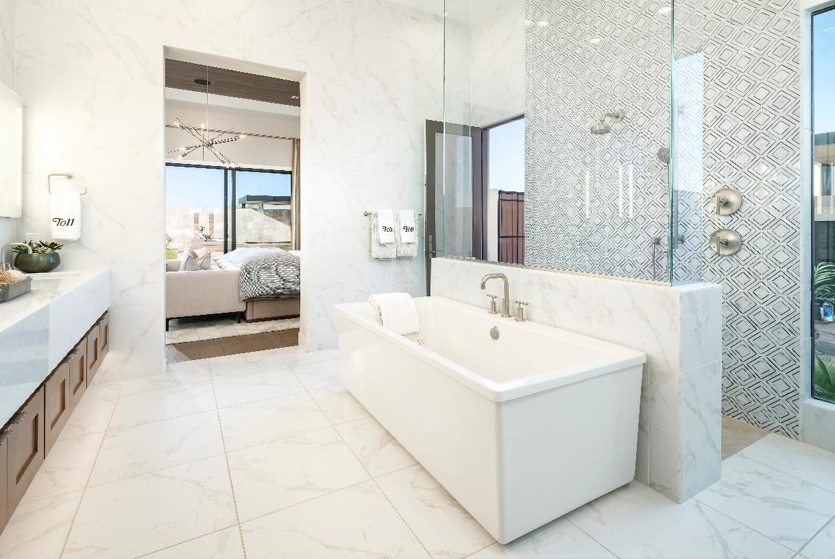 Luxe primary bath with dual vanities, freestanding tub, walk-in shower, and access to a private patio