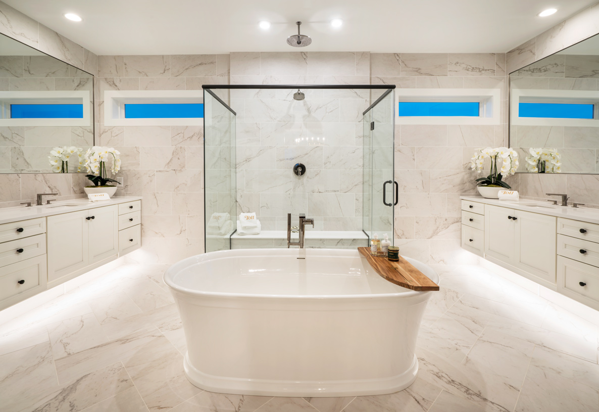Spa-like primary bath with dual vanities and glass-enclosed shower
