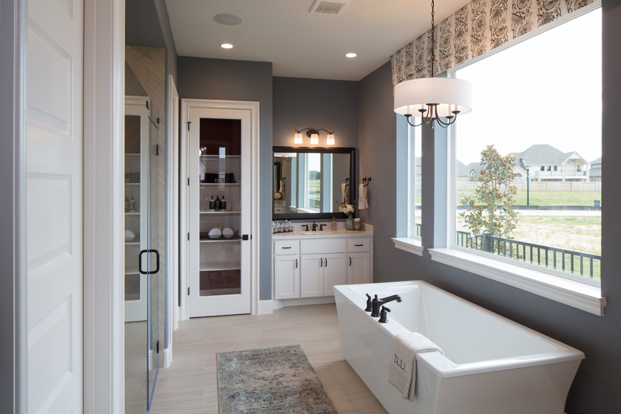 Juniper's luxurious primary bath features a free standing tub and glass-enclosed shower