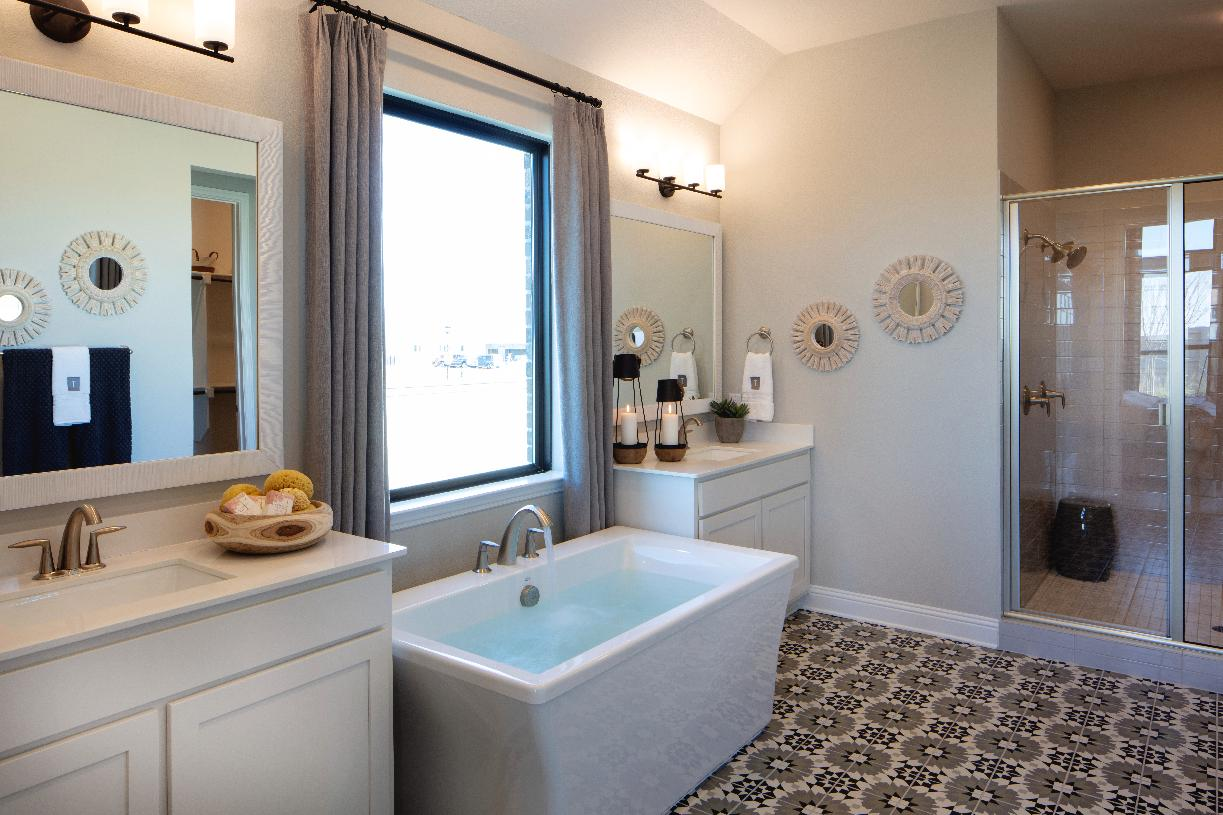 Deluxe primary bath with dual vanities, large soaking tub, and luxe shower