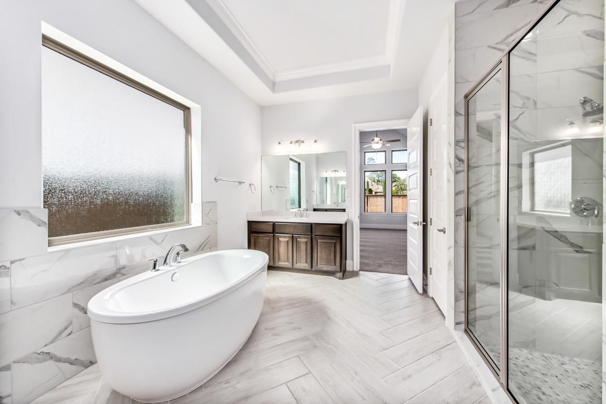 Deluxe primary bath with dual vanities, large soaking tub, and luxe glass-enclosed shower