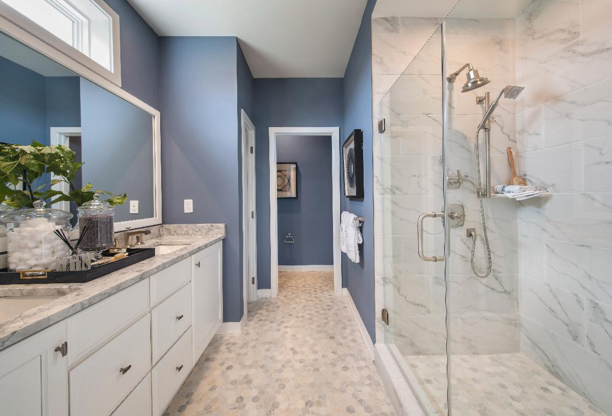 Serene primary bathroom with dual vanity and glass enclosed shower