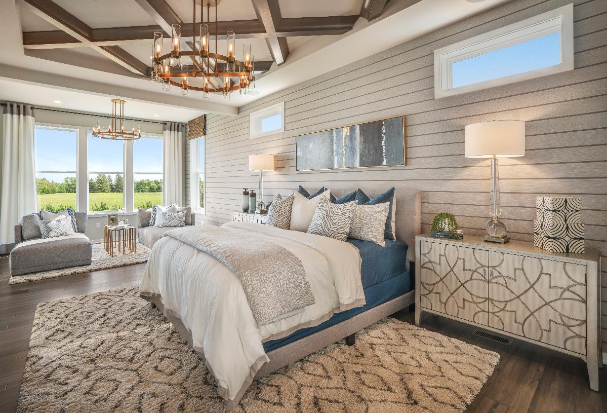 Expansive primary bedroom suite with tray ceiling