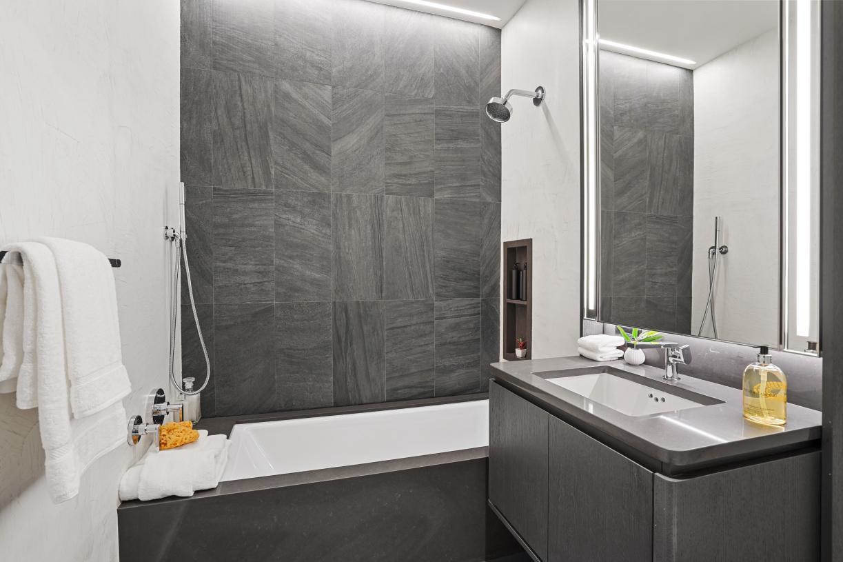 Secondary bathrooms offer Scavolini vanities, quartz countertops and Italian porcelain accent walls and flooring
