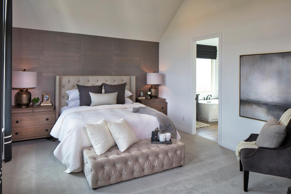 Primary bedroom features sloped ceiling and plush carpet