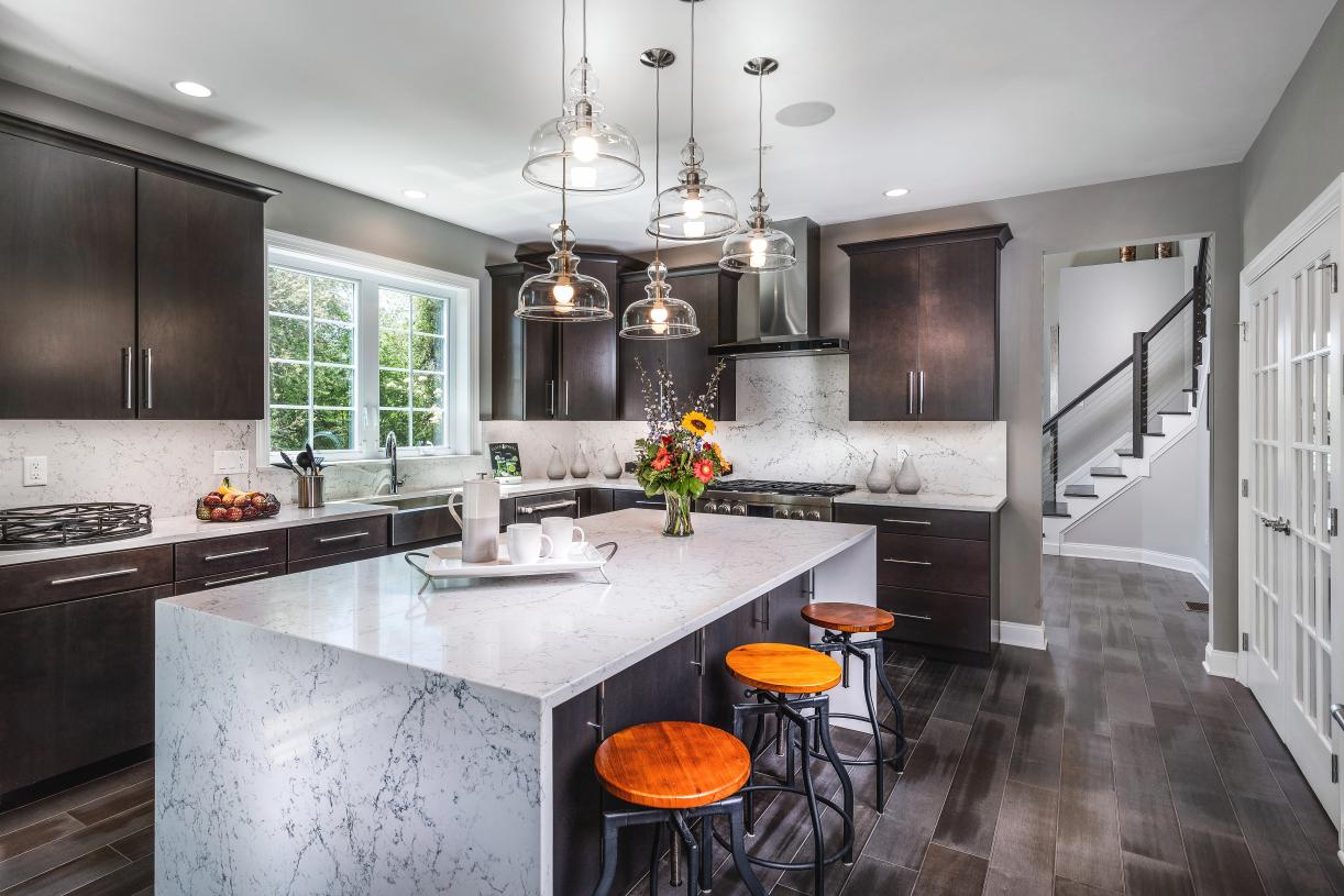 Kitchen with center island featuring a waterfall edge countertop