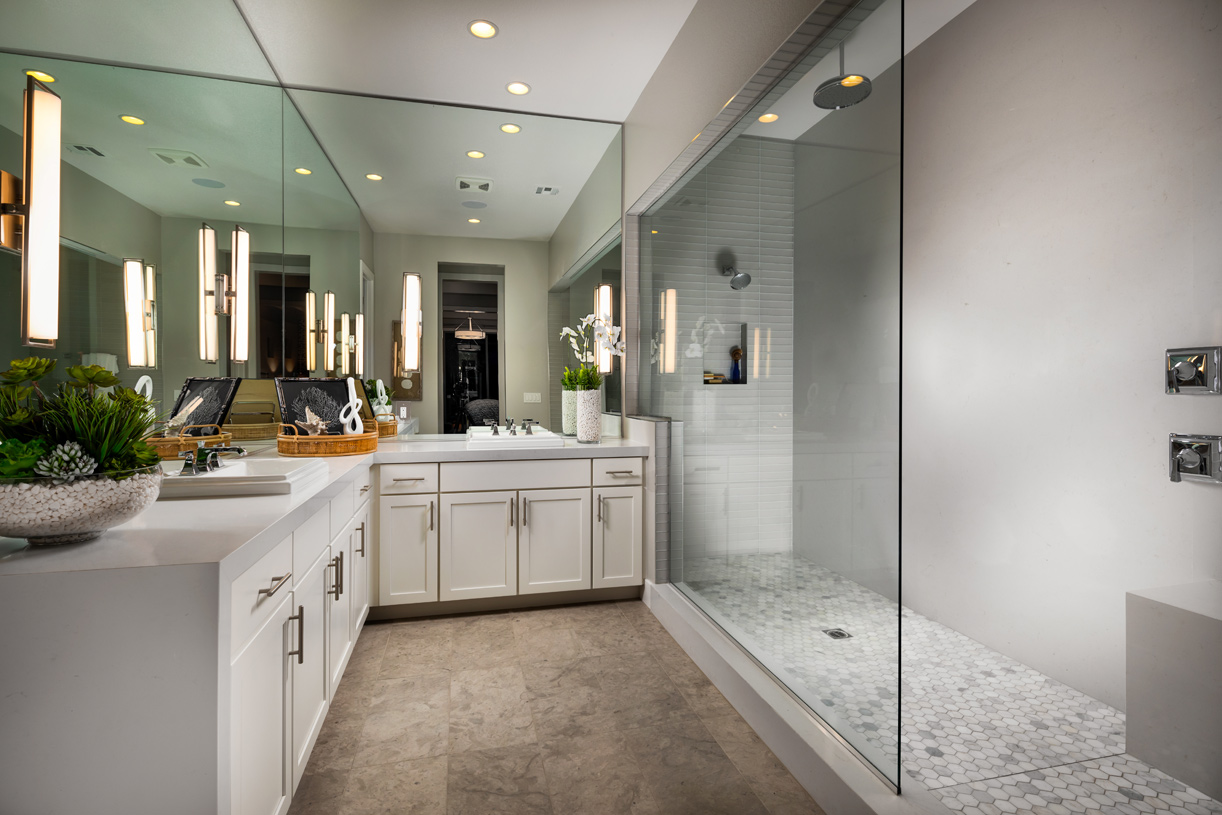 Designer finishes are showcased in this primary bath, including dual shower heads and vanities