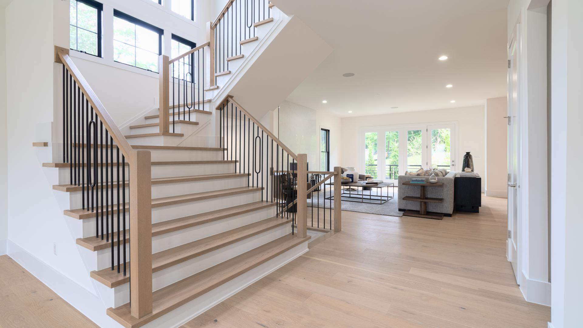 Welcoming foyer entrance with views of sprawling main level, highlighting the open main staircase with abundance of windows