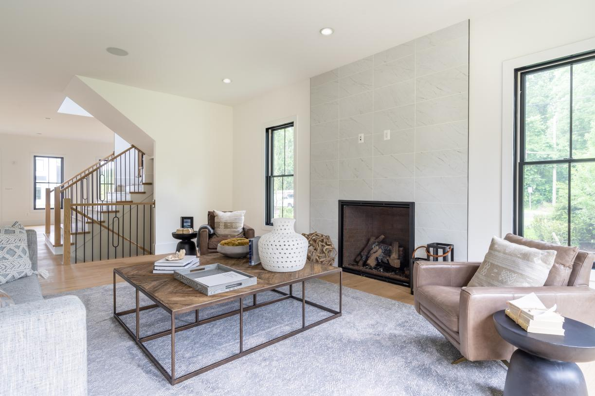 Spacious, bright great room with floor-to-ceiling ceramic tile highlighting the designer fireplace