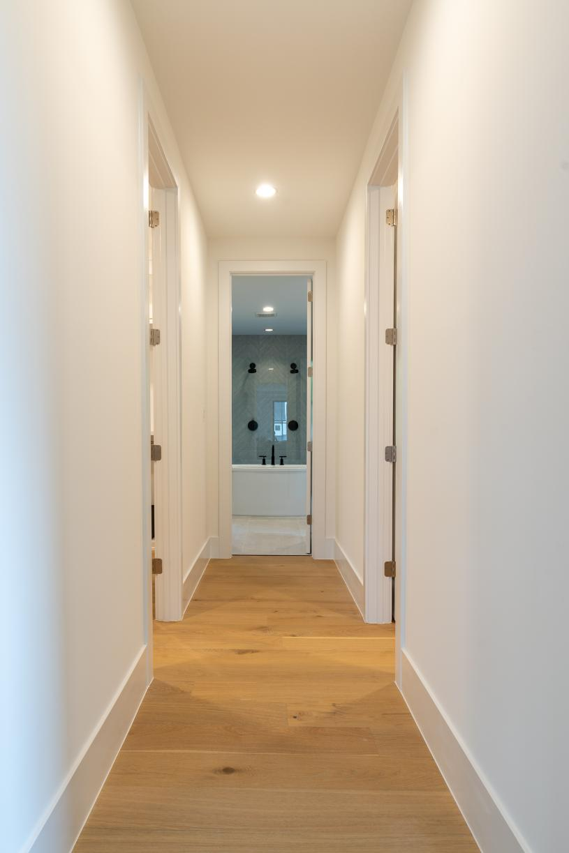 Primary suite hallway leading to luxury bath and dual walk-in closets