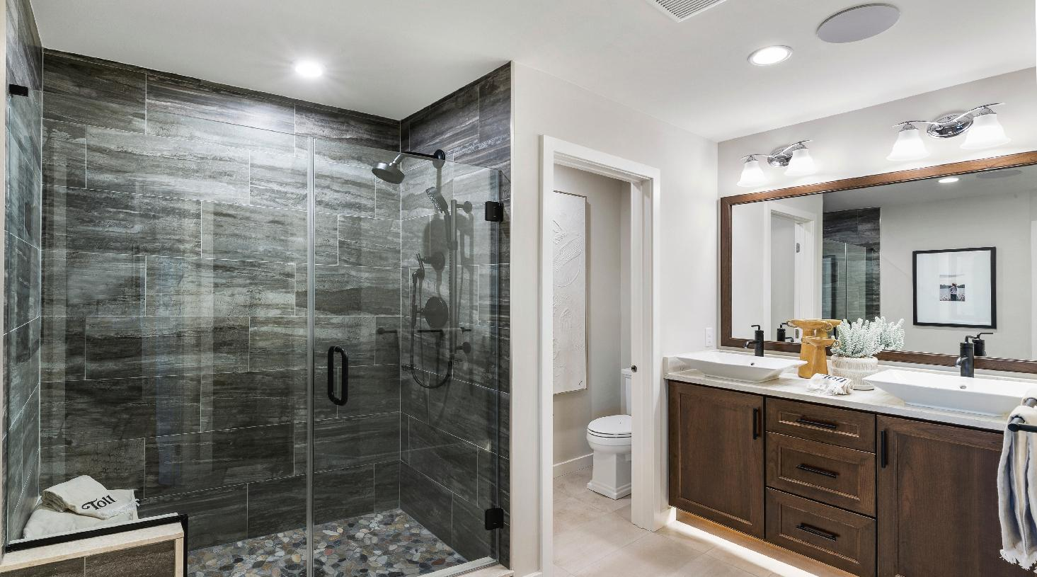 Primary bathroom with dual-sink vanity and large shower with seat