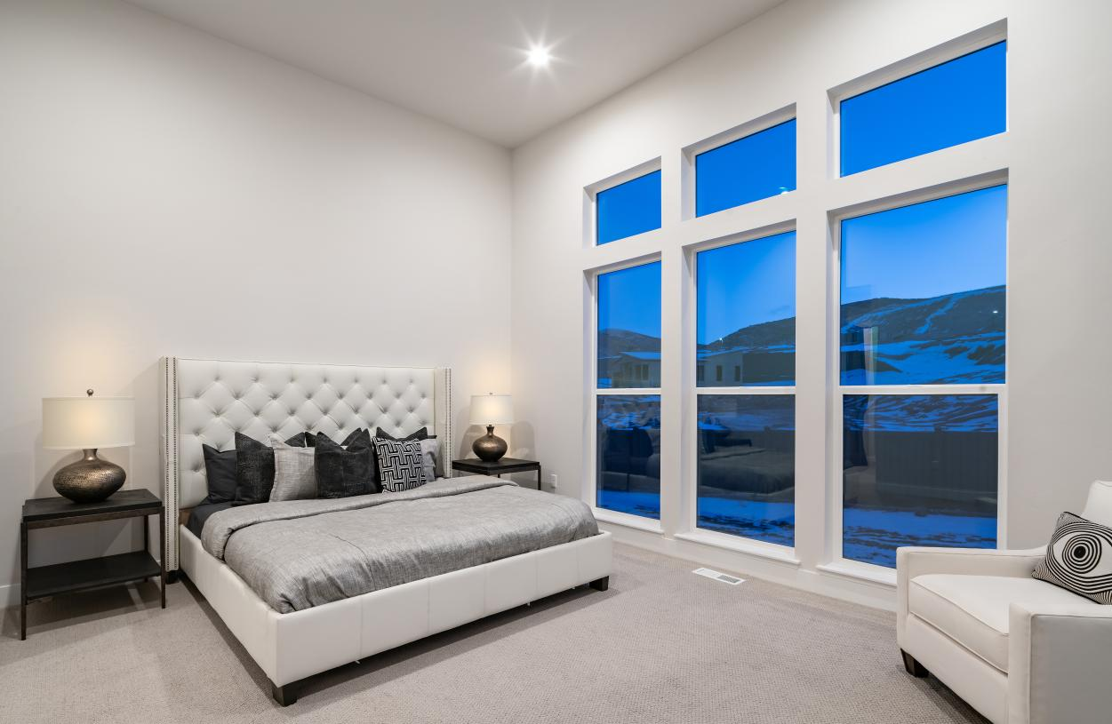 Large primary bedroom suite with ample natural light, a seating area and lavish primary bath
