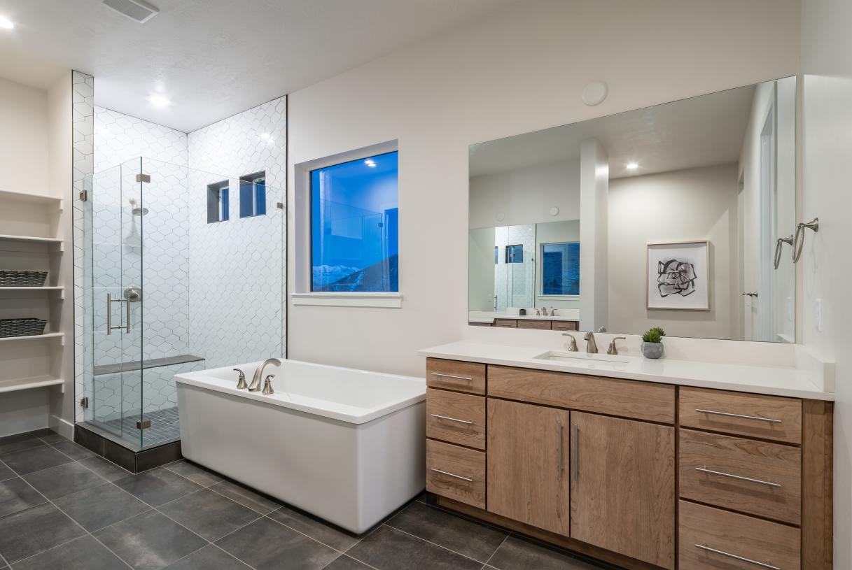 Lavish primary bathroom with a walk-in shower, large soaking tub, linen storage, and more