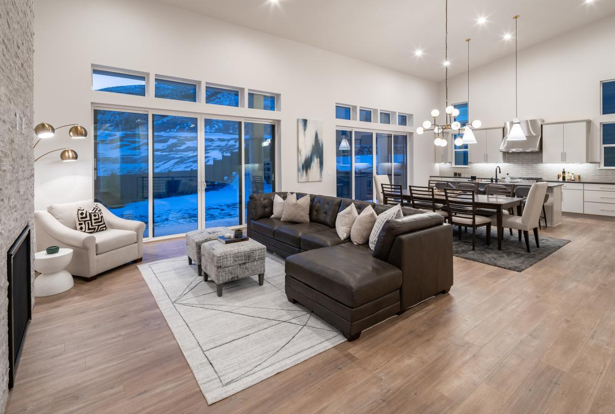 Open concept floor plans with views of the kitchen, dining area, and rear covered patio beyond
