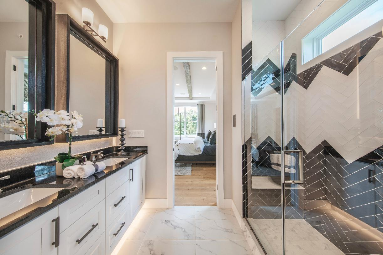 Primary bathroom with dual vanities and glass-enclosed shower