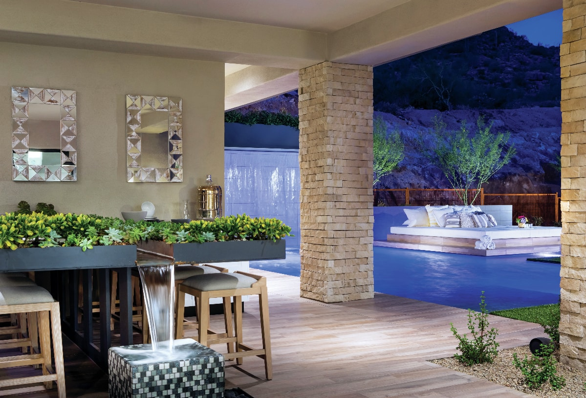 Resort-style backyard with outdoor kitchen, water features, pool and beautiful desert views