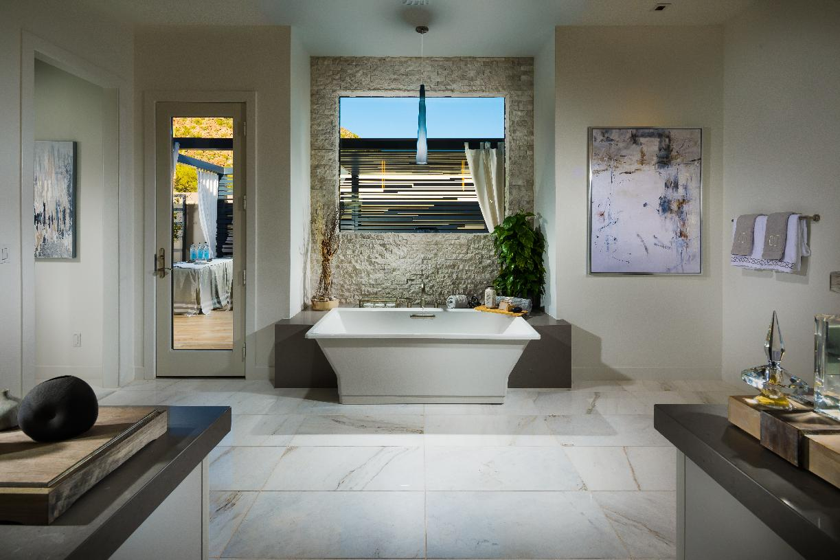 Luxe primary bathroom with dual-sink vanity, soaking tub, glass-enclosed shower and direct access to private patio