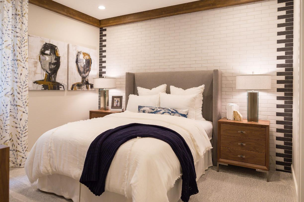 Lower level guest suite with a tile accent wall and beam post on the ceiling