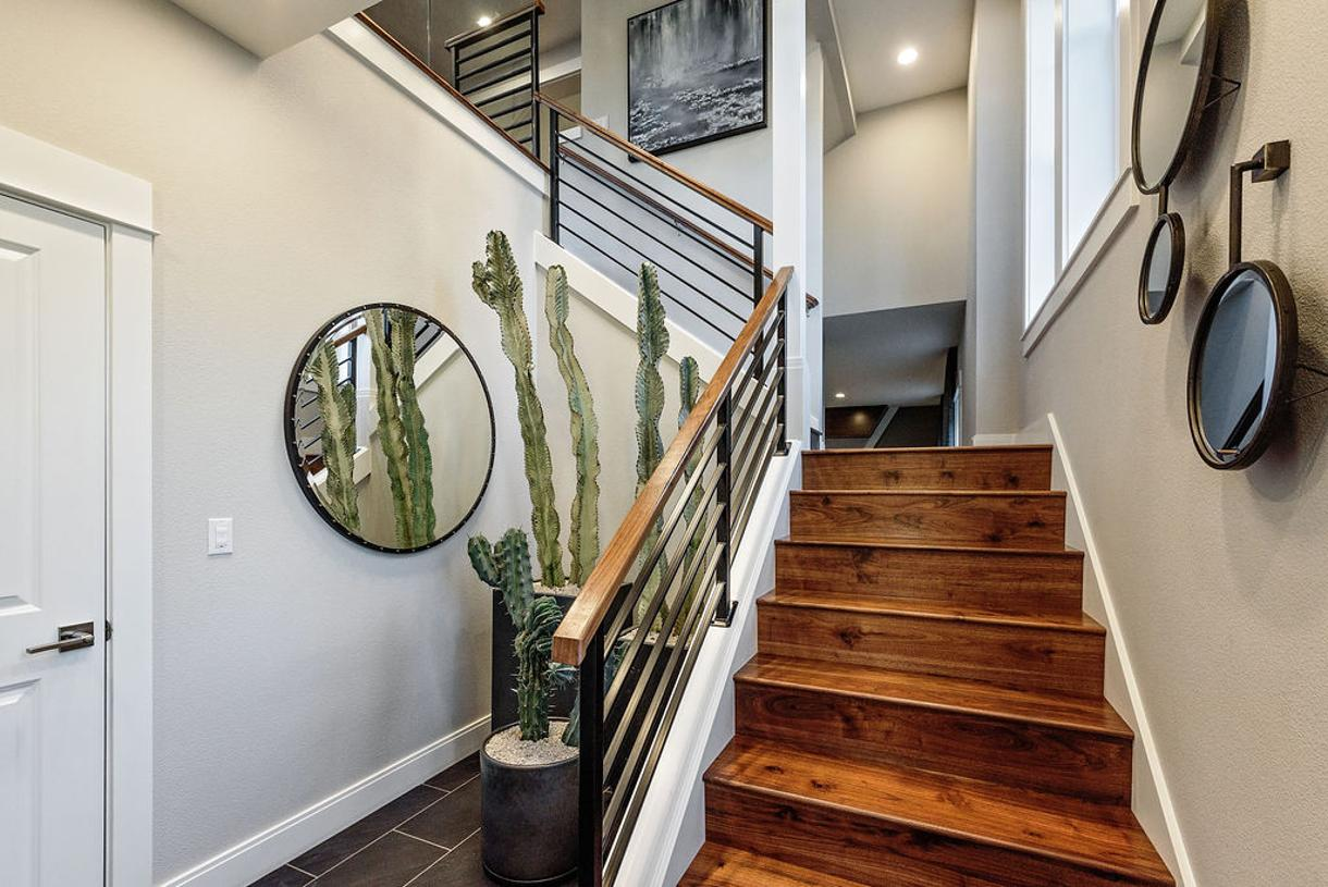 Impressive foyer entrance with a dramatic glass wall and iron stair railing