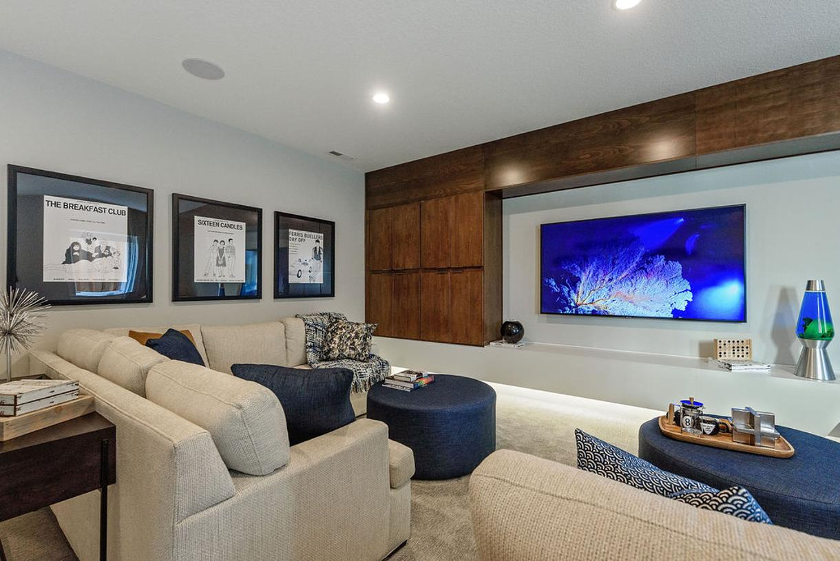 Lower level media room with custom built-in cabinets and floating shelf