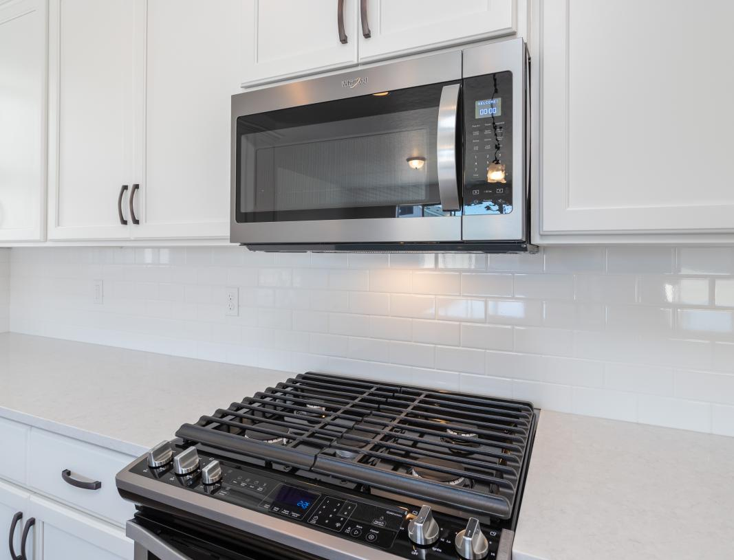 Modern stainless steel gas stove with above microwave