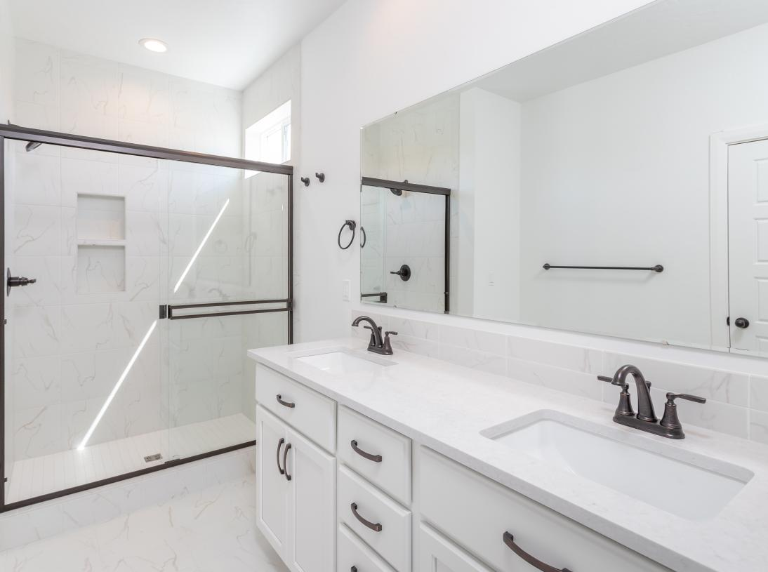 Luxurious primary bathroom with fully tiled shower and double sinks