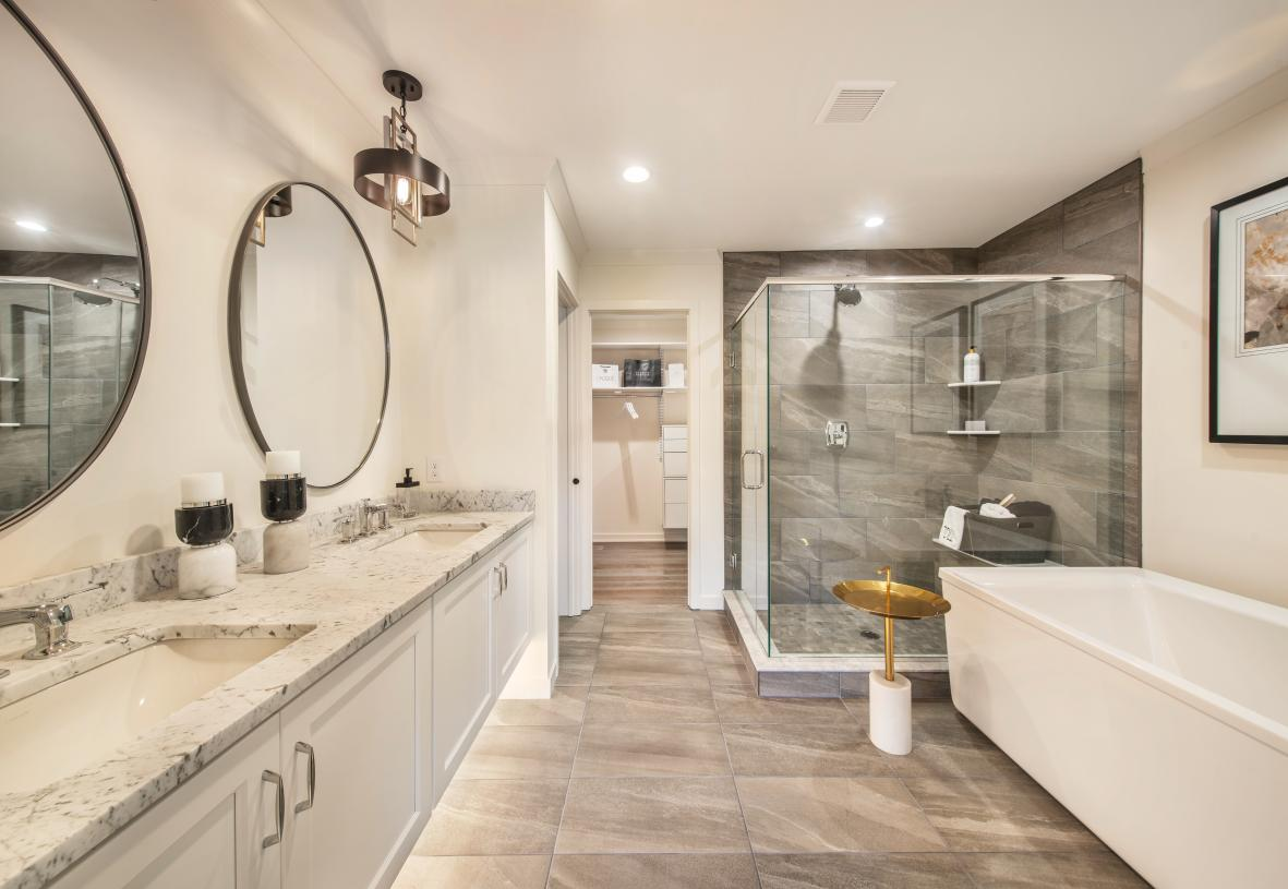 Primary bath with dual-sink vanity, luxe shower, and private water closet