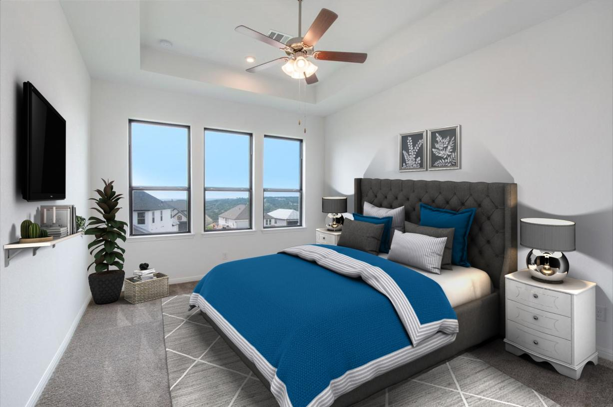 Primary bedroom suite is enhanced by an elegant tray ceiling
