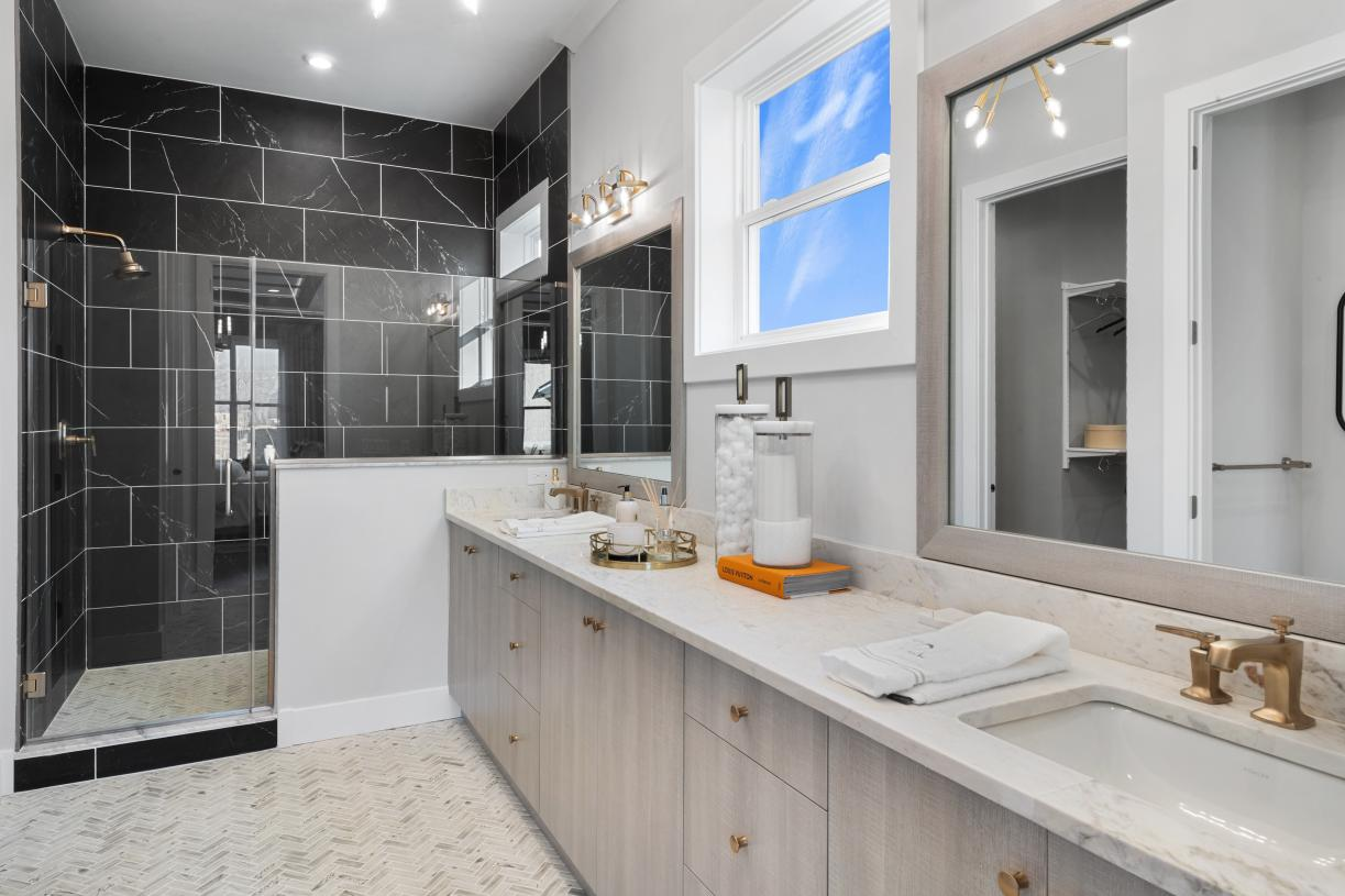 Luxe primary bathroom with dual sinks and glass enclosed shower