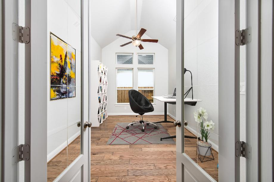 Private study with wood flooring and double glass doors, virtually staged for demonstration