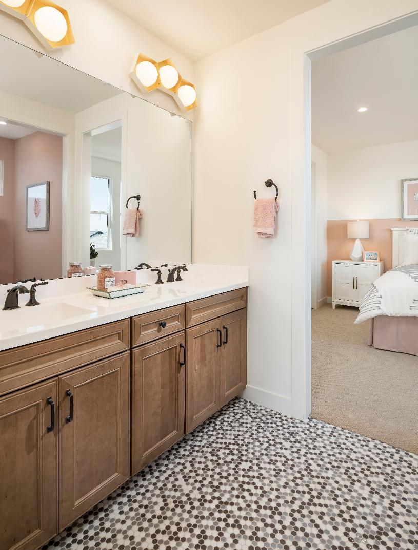 Private secondary bathroom with dual-sink vanity and mosaic tile floor