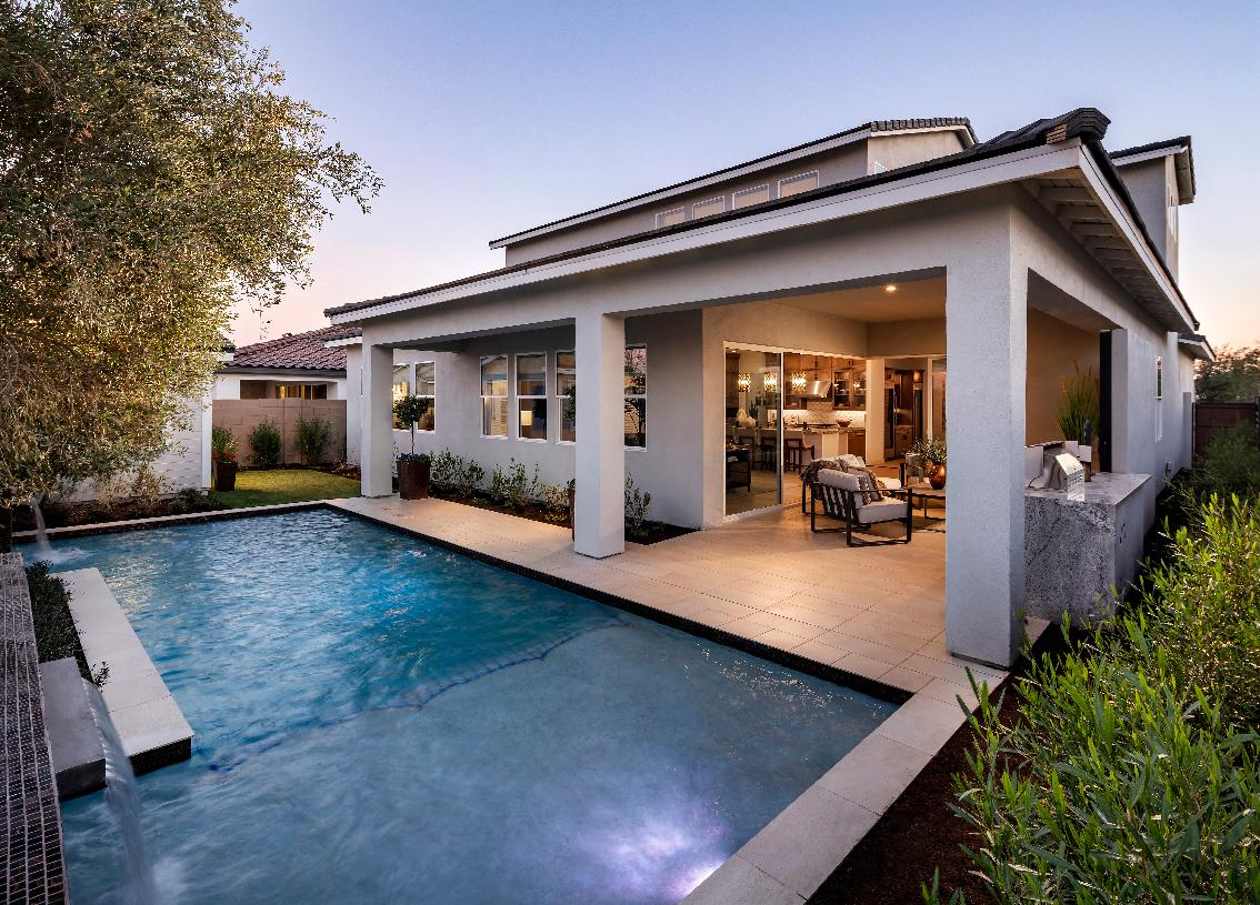 Large rear covered patio with outdoor dining area that overlooks a beautiful pool