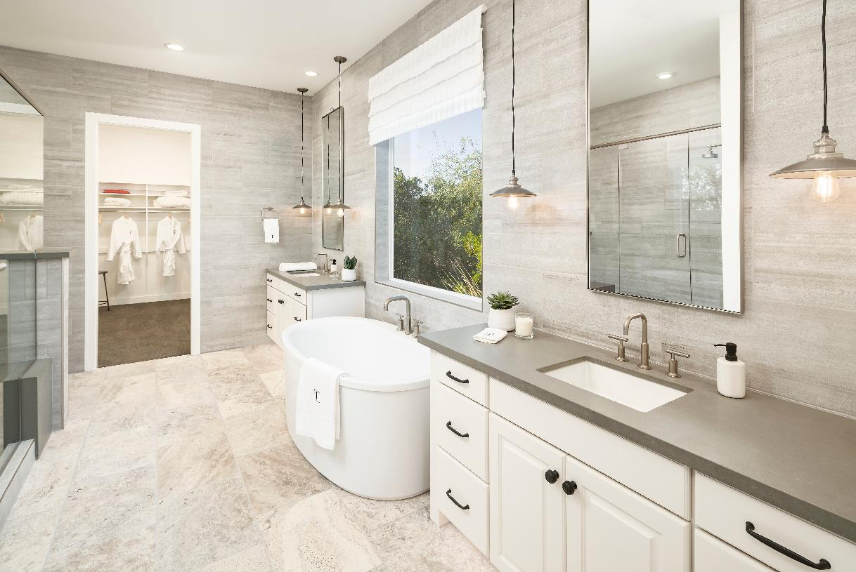 Spa-like primary bath with dual vanities, free-standing tub, and walk-in shower