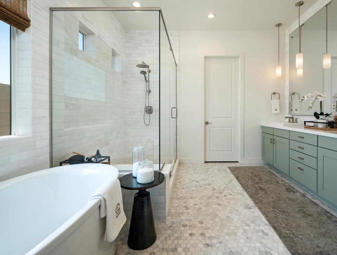 Spa-like primary bath with large soaking tub and luxe glass-enclosed shower