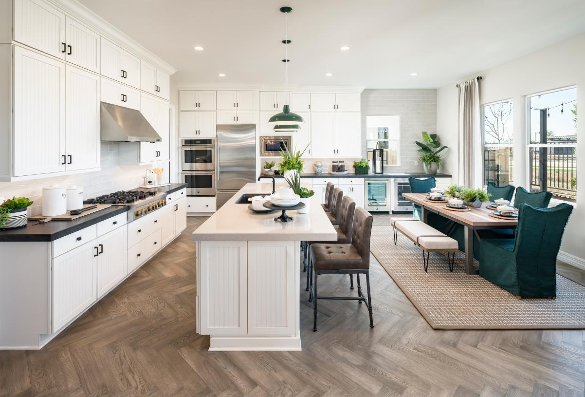 Well-appointed kitchens with large center islands, stainless steel appliances, and walk-in pantries