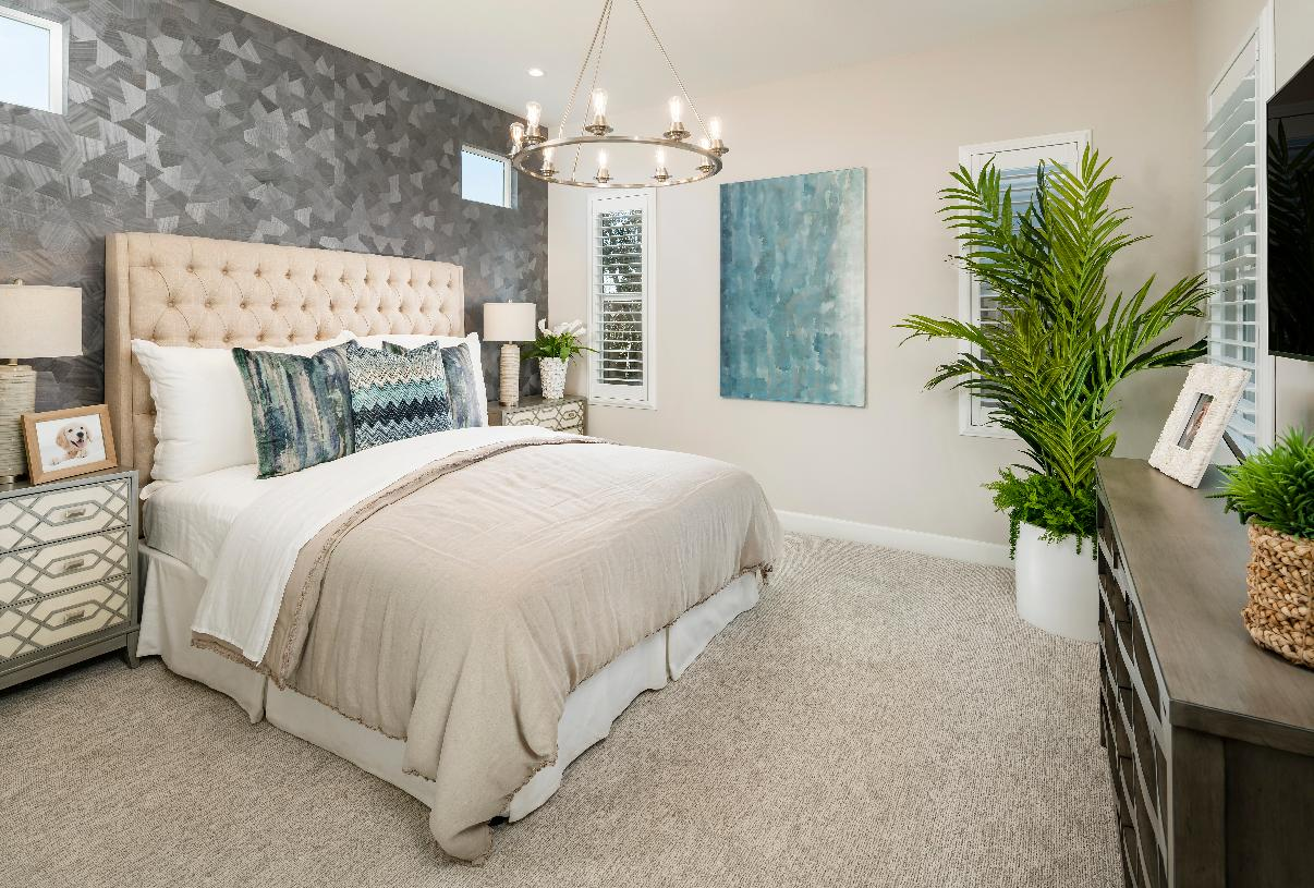Palatial primary bedroom with striking accent wall and chandelier